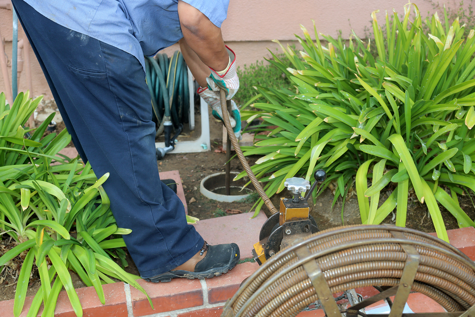 a plumber clearing a main sewer line clog