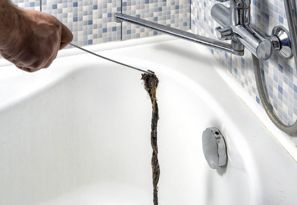 a man unclogs a bathtub drain